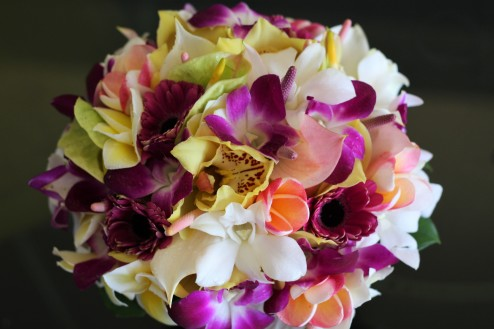 Tropical bouquet with white dendrobium orchids, purple dendrobium orchids, green cymbidium orchids, plumeria, and white anthurium.