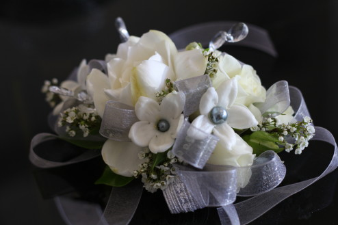 Wristlet or wrist corsage with white baby roses, gardenia, and stephanotis and grey lace ribbon