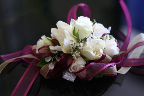 Wristlet or wrist corsage with white baby roses, gardenia, and stephanotis and purple ribbon