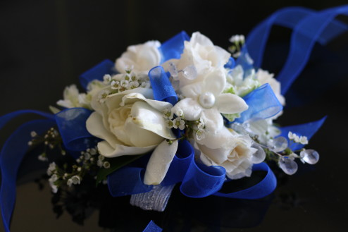 Wristlet or wrist corsage with white baby roses, gardenia, and stephanotis and blue lace ribbon